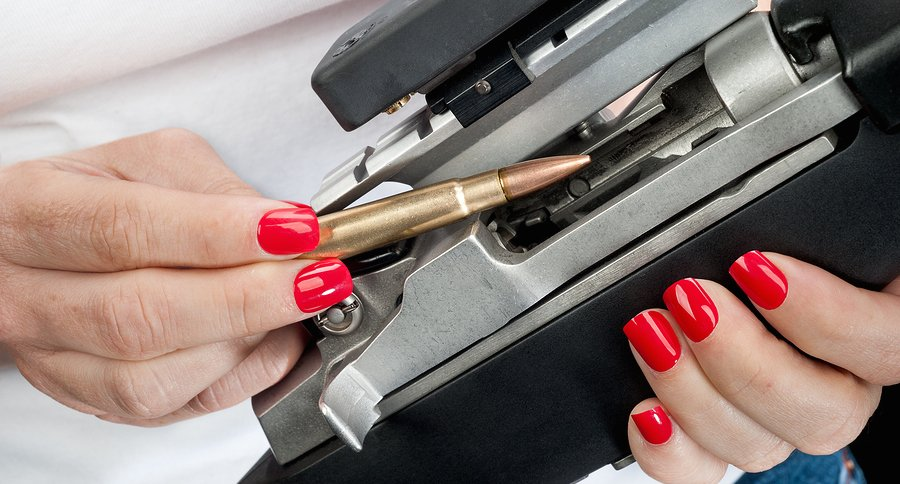 A woman with red painted fingernails loads a 223 bullet into an automatic assault rifle.