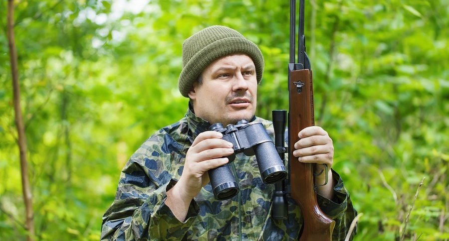 Hunter with optical rifle and binoculars in the woods